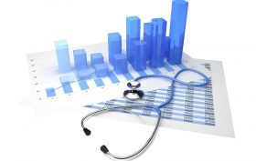 Stethoscope placed on top of the sheet with statistical graphs